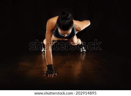 Pushup.Sporty girl doing exercise pushups on wooden floor,studio shot  - stock photo