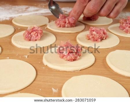 Put bit of mince in middle. Preparation Meat Dumplings. - stock photo