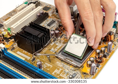 Put computer cpu chip in the socket of motherboard - stock photo