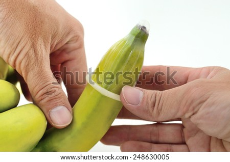 Put on condom with banana for birth control - stock photo