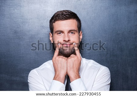Put on your smile! Handsome young man in formalwear holding fingers on his mouth and making fake smile while standing against blackboard - stock photo