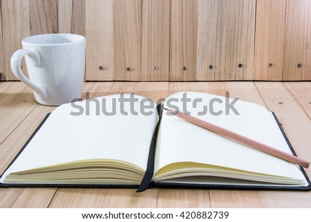 Put pencil on notebook near cup of coffee, on wood table isolate background - stock photo
