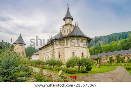 Putna historic monument Orthodox Monastery in Moldavia region of Romania with incredible stone architecture and a beautiful green garden on a cloudy rainy day - stock photo