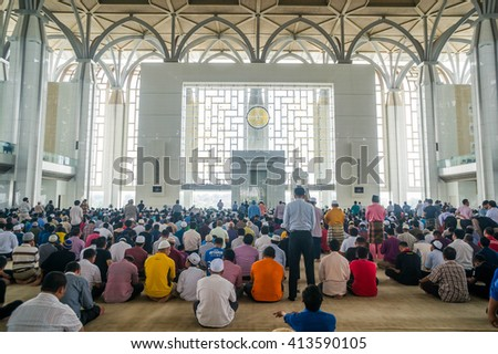 PUTRAJAYA - APRIL 30: Muslim performing Friday prayers at Tuanku Mizan Mosque on April 30, 2015 in Putrajaya Malaysia. Friday prayer is perform just after noon in the place of dhuhr - stock photo