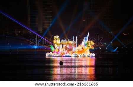 PUTRAJAYA, MALAYSIA- JUNE 21, 2014 :Penang floats cruising at lake during FLORIA night show in Putrajaya, Malaysia, showcasing their own unique tourism attraction. - stock photo