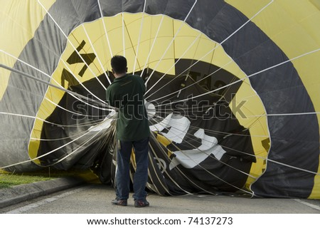 PUTRAJAYA, MALAYSIA-MAR 19:Crew members help preparing a balloon at the 3rd Putrajaya International Hot Air Balloon Fiesta on Mar 19, 2011 in Putrajaya.More than 300,000 people visit this year event