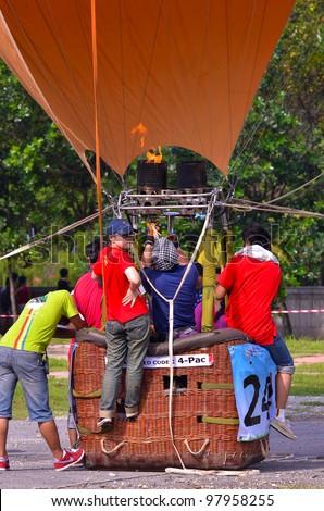 PUTRAJAYA, MALAYSIA-MAR 17: Crew members released flame into the balloon and docking at the 4th Putrajaya International Hot Air Balloon Fiesta Mar 17, 2012 Putrajaya. - stock photo