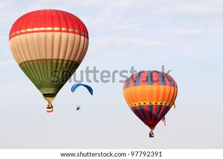 PUTRAJAYA, MALAYSIA-MAR 16: Hot Air balloon and paraglider in flight at the 4th Putrajaya International Hot Air Balloon Fiesta Mar 16, 2012 in Putrajaya. - stock photo