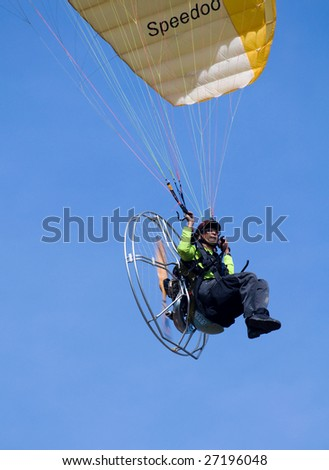 PUTRAJAYA, MALAYSIA - MARCH 21:  A motor powered paraglider flies at the first International Hot Air Balloon fiesta in Putrajaya on March 21, 2009 in Putrajaya, Malaysia.