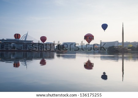 PUTRAJAYA, MALAYSIA - MARCH 30:Multi shaped hot air balloons floating over sunrise skies at the 5th Putrajaya International Hot Air Balloon Fiesta in Putrajaya, Malaysia on March 30, 2013 - stock photo