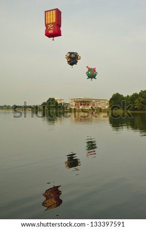 PUTRAJAYA, MALAYSIA - MARCH 30:Three hot air balloons fly across the lake during 5th Putrajaya International Hot Air Balloon Fiesta at Presint 2, Putrajaya on March 30, 2013. - stock photo