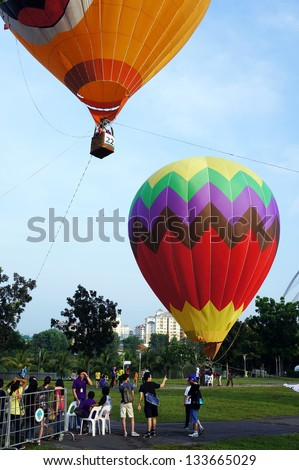 PUTRAJAYA, MALAYSIA-MARCH 29: Visitors queuing for hot air balloons ride at the 5th Putrajaya International Hot Air Balloon Fiesta 29 March, 2013 in Putrajaya. - stock photo