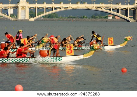 PUTRAJAYA, MALAYSIA - OCTOBER 21: Unidentified teams participate in IDBF Cancer Survivors World Cup 2011 & Malaysia International Dragon Boat Festival 2011 in Putrajaya, Malaysia on October 21, 2011. - stock photo