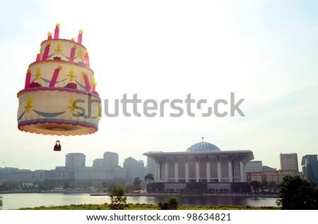 PUTRAJAYA-MARCH 18: Unique Birthday Cake balloon flies over Putrajaya Steel Mosque at the 4th Putrajaya International Hot Air Balloon Fiesta on March 18, 2012 in Putrajaya, Malaysia. - stock photo