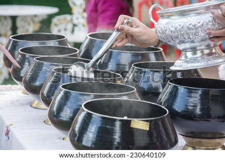 puts food offerings in a Buddhist monk's alms bowl - stock photo