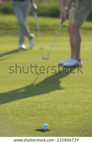 putt goes in the hole / even though you're frustrated / this makes you come back  - stock photo