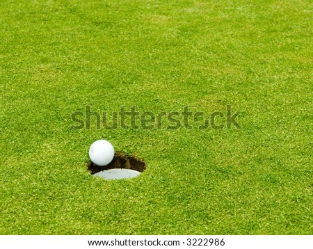 Putted golfball dropping into the cup. Shallow DOF focus placed crisply at location of the cup leaves defocused grassy area for text and design elements. - stock photo