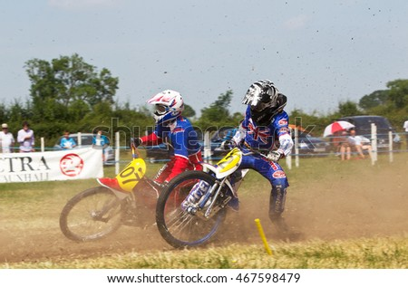 PUTTENHAM, UK - JULY 14: Two unnamed riders competing in the Puttenham grasstrack racing event ride the top corner of the circuit at speed on July 14, 2013 in Puttenham.