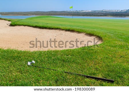 Putters and ball lying on golf course. - stock photo