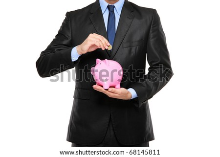 Putting a coin into a piggy bank isolated on white background - stock photo