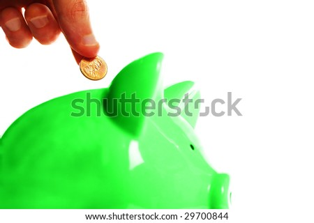 putting a penny in a green piggy bank, on white - stock photo