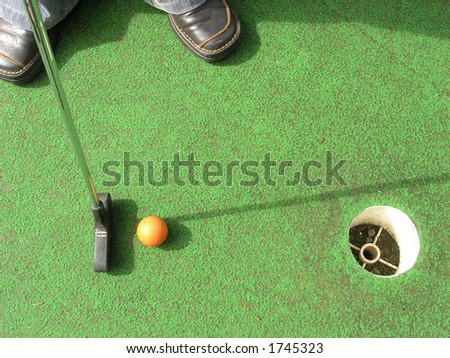 Putting at a mini golf leisure facility. - stock photo