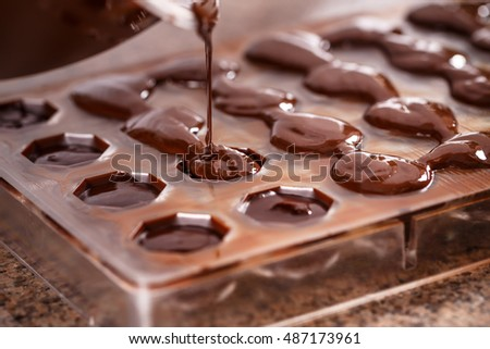 Putting chocolate in mold, make praline