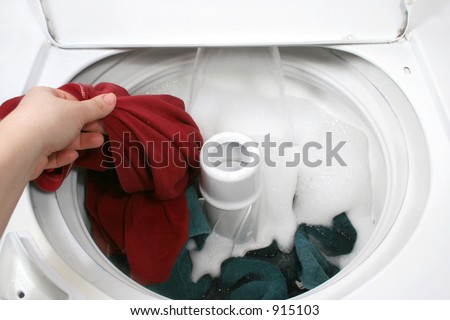 putting clothes into washer - stock photo