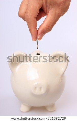 Putting coin into piggy bank - stock photo