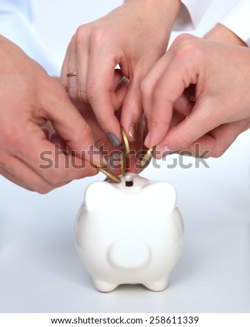 Putting coin into the piggy bank . - stock photo