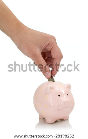 putting coin into the piggy bank - stock photo
