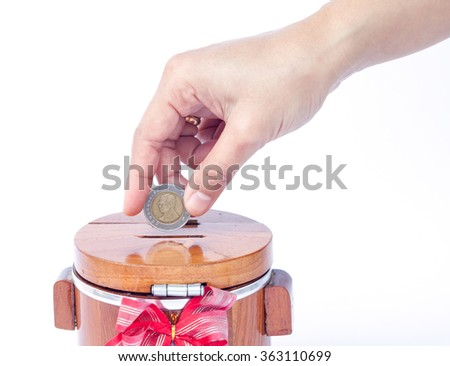 Putting coin to save money, stock photo