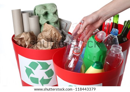 Putting empty bottles into recycling bins, closeup - stock photo