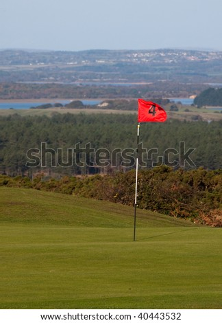 Putting green and flag on an English links golf course - stock photo