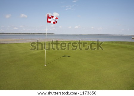putting green on golf course overlooking ocean - stock photo