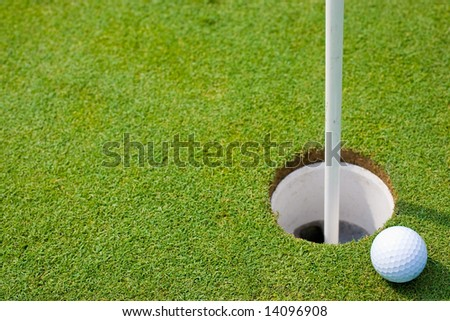 Putting Green with Ball on Edge of the Cup - stock photo
