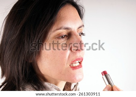 Putting lipstick on - stock photo