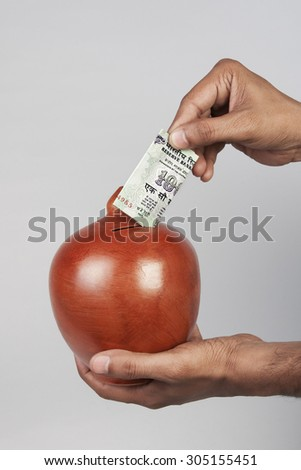 Putting money in a piggy bank - stock photo