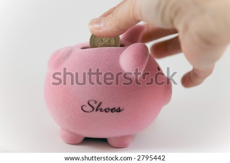 Putting money into a Piggy bank on a white background