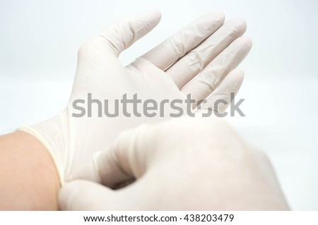 putting on disposable sterile white gloves on white background
