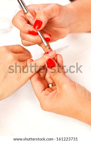 Putting on transparent artificial nail to a woman's little finger