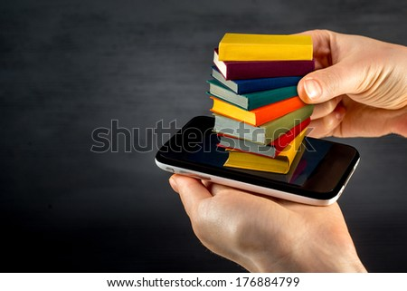 putting or download colorful books to the smart phone - stock photo