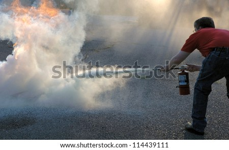 Putting out a fire with a powder type extinguisher. - stock photo