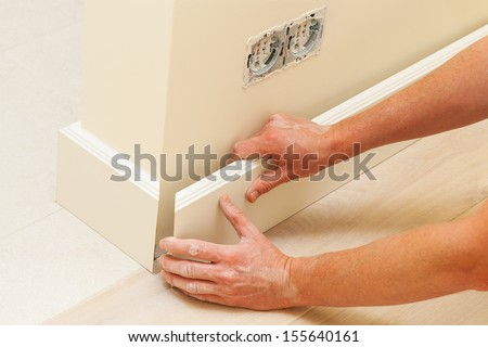 Putting skirting board to a fresh paint wall - stock photo