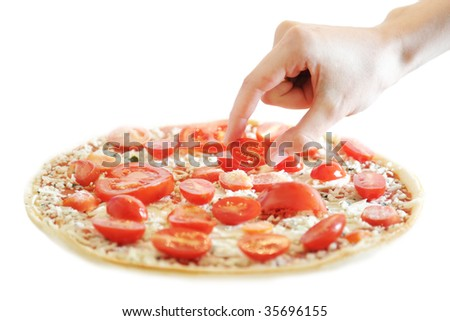 Putting tomatoes on a vegetarian pizza - stock photo