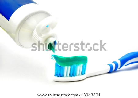 Putting tooth paste on brush over white background.