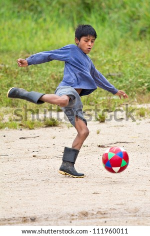 PUYO, ECUADOR - JANUARY 7: Unidentified Quechua boy plays soccer on January 7, 2012 in Puyo, Ecuador. Quechua are the largest South American ethnic group but only few live in the Amazon lowlands. - stock photo