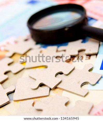 Puzzle and magnifier on documents. - stock photo