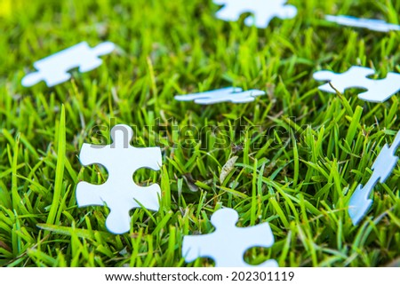 Puzzle background in the grass - stock photo