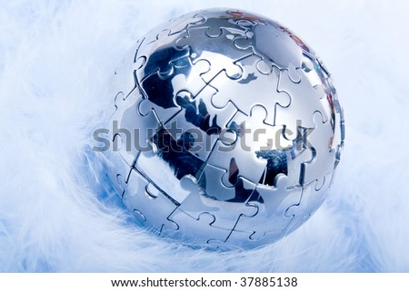 Puzzle Globe on very soft feather - stock photo